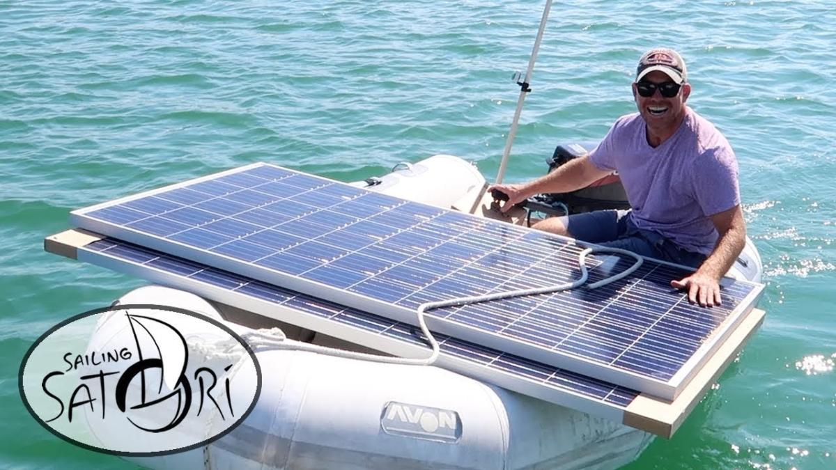 Picture of Nick hauling two oversized solar panels on the dinghy