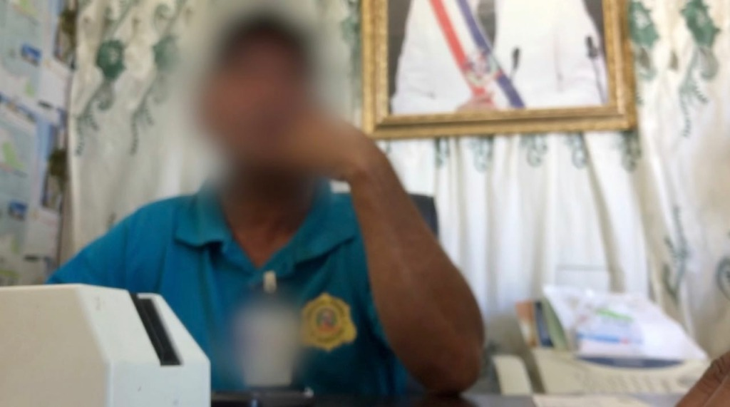 Photo of a man at a desk in the immigration office